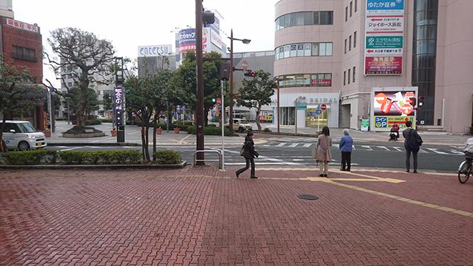 改札から鍛冶町方面へくだり、すぐ近くの交差点の左手側の横断歩道を直進